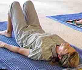 Lying on floor, knees bent, feet standing